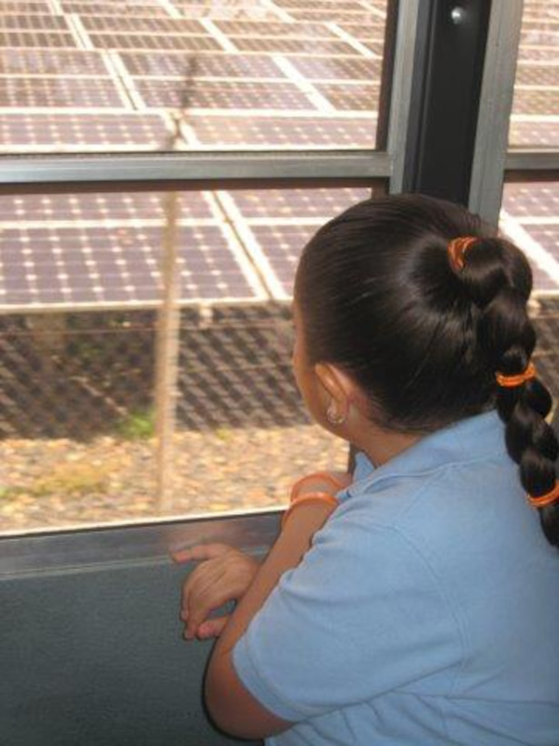 As her school bus arrives at a project site at Fort Buchanan, Puerto Rico, a first grade student from Antilles Elementary School views the solar panels that were installed by Fort Buchanan's Environmental Division as an alternative energy source.