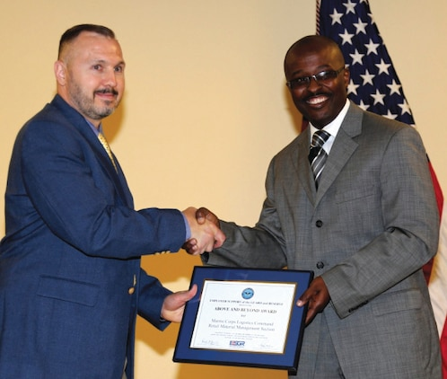 Andrew Trout, section supervisor, Retail Inventory Support Section, Logistics Services Management Center, Marine Corps Logistics Command, (left), receives Above and Beyond Award from Michael Bryant, field representative to U.S. Congressman Sanford D. Bishop Jr., 2nd Congressional District, Georgia, and state representative from the Employer Support of the Guard and Reserve, during a ceremony held at LOGCOM Headquarters, May 28.