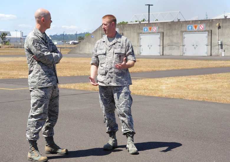 Senior Master Sgt. Jeffrey Reynolds, assigned to the 142nd Fighter Wing Maintenance Group, right, takes Ronald C. Anderson Jr., Command Chief Master Sgt., 1st Air Force, left, on a tour of the munitions area at the Portland Air National Guard Base, Ore., June 10, 2014. (Air National Guard photo by Tech. Sgt. John Hughel, 142nd Fighter Wing Public Affairs/Released)