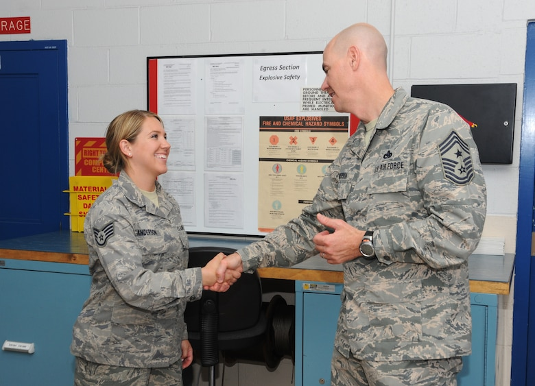 Ronald C. Anderson Jr., Command Chief Master Sgt., 1st Air Force, right, gives his Chief Coin to Staff Sgt. Jennifer Anderson, left, of the 142nd Fighter Wing Maintenance Group, during his tour of the Portland Air National Guard Base, Ore., June 10, 2014. (Air National Guard photo by Tech. Sgt. John Hughel, 142nd Fighter Wing Public Affairs/Released)
