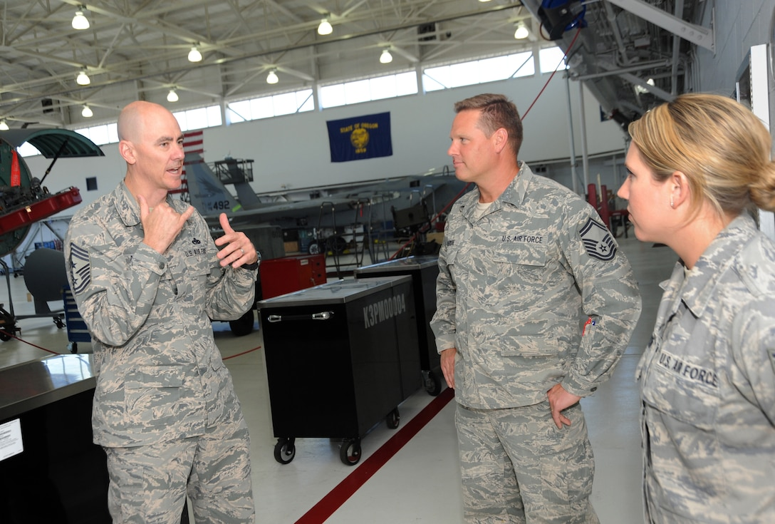 Ronald C. Anderson Jr., Command Chief Master Sgt., 1st Air Force, left, talks to Master Sgt. Landon Selfridge, center, and Staff Sgt. Jennifer Anderson, right, of the 142nd Fighter Wing Maintenance Group, during his tour of the Portland Air National Guard Base, Ore., June 10, 2014. (Air National Guard photo by Tech. Sgt. John Hughel, 142nd Fighter Wing Public Affairs/Released)