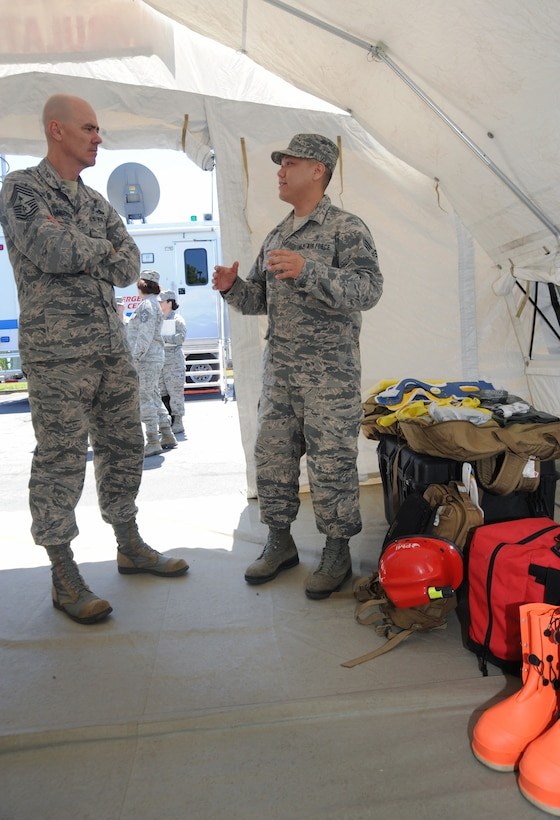 Senior Airman Charlie Phu, right, assigned to the 142nd Medical Group, describes some of the protection gear used by the CBRNE Enhanced Response Force Packages (CERFP) to Ronald C. Anderson Jr., Command Chief Master Sgt., 1st Air Force, left, during his visit to the Portland Air National Guard Base, Ore., June 10, 2014. (Air National Guard photo by Tech. Sgt. John Hughel, 142nd Fighter Wing Public Affairs/Released)