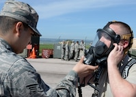 Senior Airman  Roger Pedraza, 28th Medical Operations Squadron bioenvironmental technician, assists Airman 1st Class Ronald Reynolds, 28th Civil Engineer Squadron emergency management technician, with his respiratory mask during an Integrated Base Emergency Response Capabilities Training at Ellsworth Air Force Base, S.D., May 22, 2014. The mask and Level-A suit protect emergency responders from hazardous materials and contaminated environments. (U.S. Air Force photo by Senior Airman Anania Tekurio/Released)