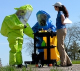 Morgan Lindsey, Alliance Solutions Group Inc. analyst, evaluates how well Staff Sgt. Kathleen Couillard, 28th Medical Operations Squadron bioenvironmental technician, and Airman 1st Class Ronald Reynolds, 28th Civil Engineer Squadron emergency management technician, perform a task during an Integrated Base Emergency Response Capabilities Training at Ellsworth Air Force Base, S.D., May 22, 2014. Couillard and Reynolds were evaluated on actions they would take in response to an unsafe environment and how to implement proper safety measures. (U.S. Air Force photo by Senior Airman Anania Tekurio/Released))