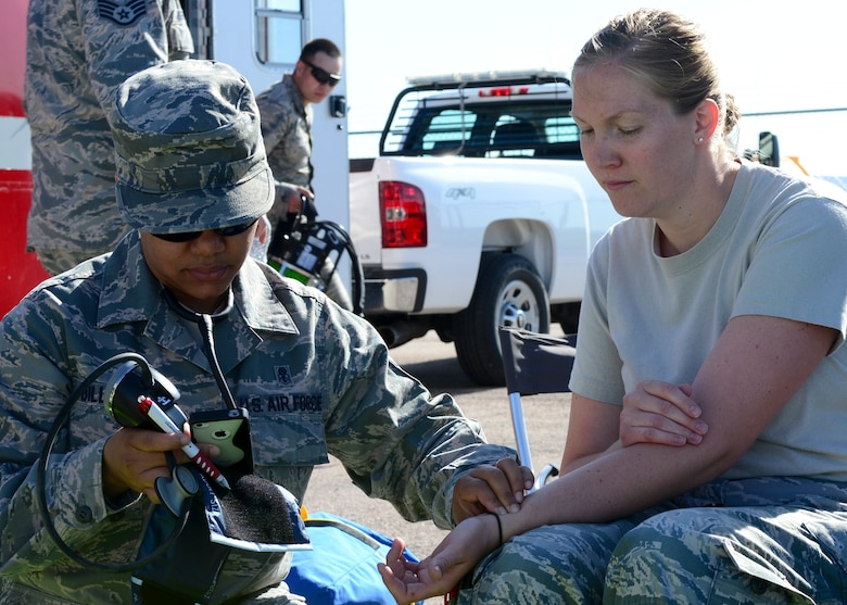 Master Sgt. Jaqueline Billups, 28th Medical Operations Squadron clinical medicine flight chief, monitors the heart rate of Staff Sgt. Kathleen Couillard, 28th MDOS bioenvironmental technician, during an Integrated Base Emergency Response Capabilities Training at Ellsworth Air Force Base, S.D., May 22, 2014. The week-long exercise provided Airmen with training opportunities related to honing chemical, biological, radiological and nuclear defense skills. (U.S. Air Force photo by Senior Airman Anania Tekurio/Released)