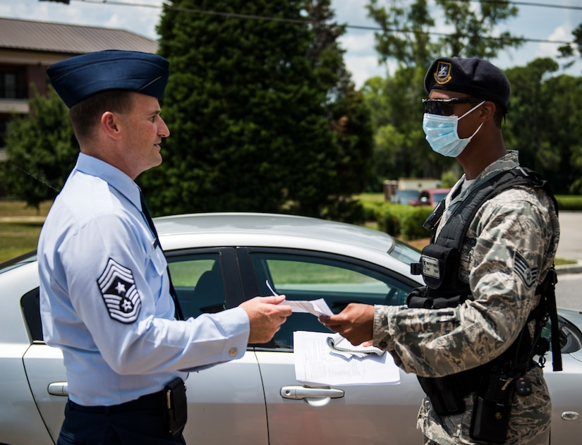 Chief Master Sergeant Mark Bronson, 628th Air Base Wing command chief, participates in the Disease Containment Exercise by checking in with a 628th Security Forces Squadron member before being medically evaluated by a member of the 628th Medical Group to determine if he had been infected June 4, 2014, at Joint Base Charleston, S.C. Personnel from the 437th Airlift Wing and the 628th Air Base Wing, along with Naval Nuclear Power Training Command  Sailors and approximately 85 volunteers participated in the exercise. (U. S. Air Force photo/ Senior Airman Dennis Sloan)