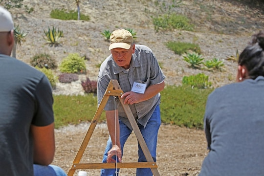 Lief Christenson, an instructor for the Agricultural Development for Armed Forces Pre-Deployment Training, demonstrates how to use a level to prepare a ditch at the San Diego Botanical Gardens in Encinitas, Calif., June 10, 2014. The training is designed to prepare service members to provide humanitarian aid in allied countries.