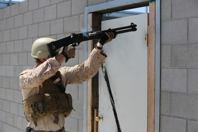 A Marine from 1st Reconnaissance Battalion fires breaching rounds into a door hinge during a Methods of Entry proficiency training exercise aboard Camp Pendleton Calif., June 10.  During the exercise, raid scenarios were tailored for the event to keep the Marines in an operational mindset while honing their skill set for future deployments as the Maritime Raid Force in support of Marine Expeditionary Units.