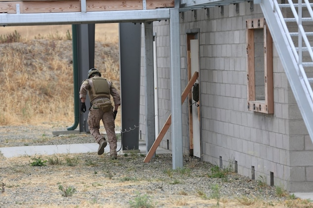 A Marine from 1st Reconnaissance Battalion runs for cover after placing an explosive charge during a Methods of Entry proficiency training exercise aboard Camp Pendleton Calif., June 10.  During the exercise, raid scenarios were tailored for the event to keep the Marines in an operational mindset while honing their skill set for future deployments as the Maritime Raid Force in support of Marine Expeditionary Units.