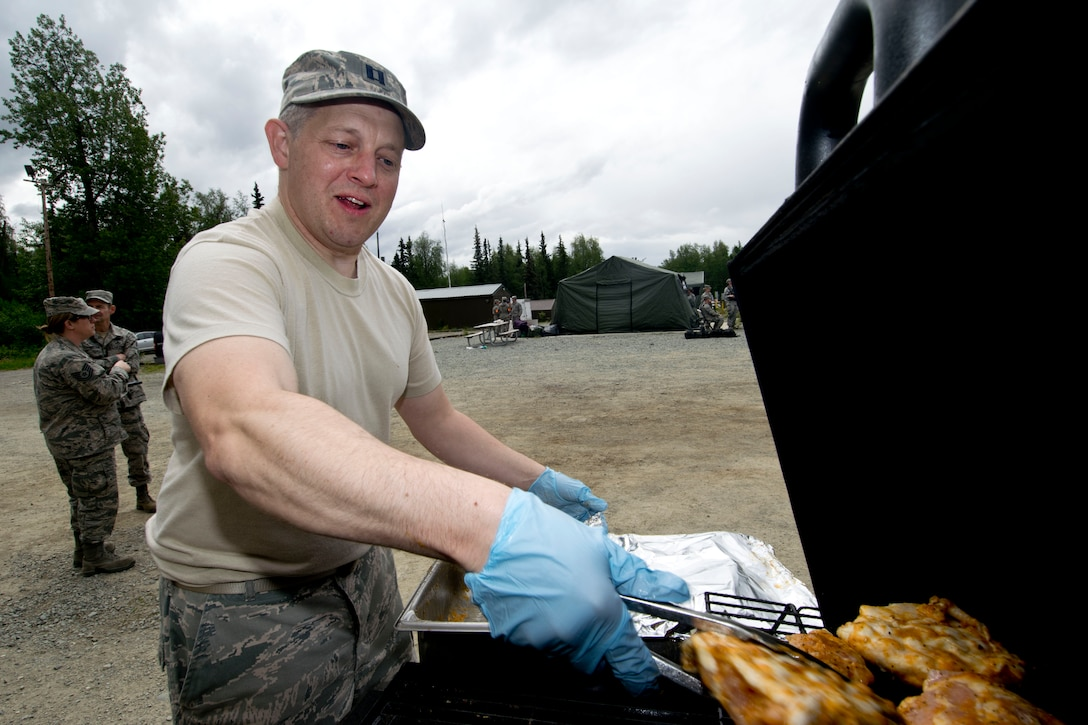 JOINT BASE ELMENDORF-RICHARDSON, Alaska -- Capt. Luke Davis, deputy commander of the 176th Force Support Flight prepares food for airmen conducting training here at Camp Mad Bull here June 9, 2014. The 176th Mission Support Group and the 176th Medical Group participated as part of Polar Guardian 14-2. (U.S. Air National Guard photo by Capt. John Callahan/ Released)