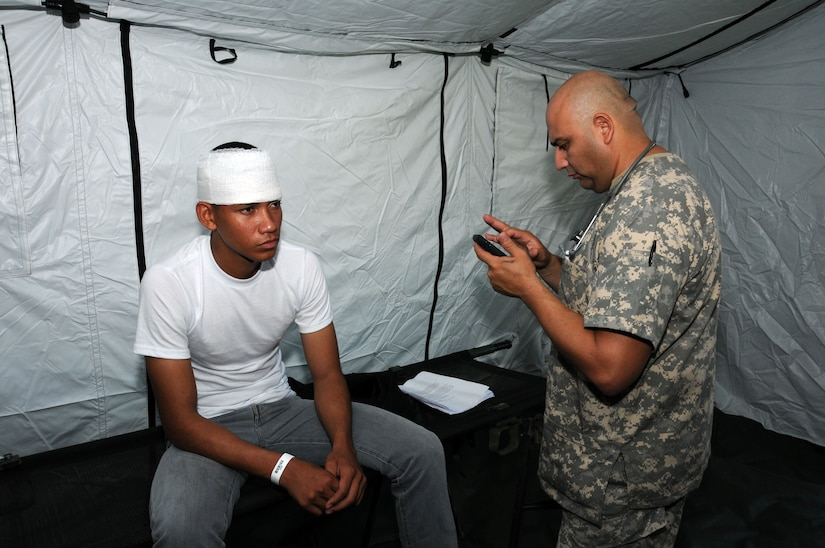After treating a hurricane victim for a head injury,U. S. Army Sgt. Manuel Olivarez, MEDEL emergency medical technician, enters the patient's treatment information into the Global MedAid program.  In preparation for the 2014 hurricane season, the Joint Task Force-Bravo Medical Element (MEDEL) conducted a humanitarian assistance/disaster response (HA/DR) exercise at Soto Cano Air Base, Honduras June 12, 2014.  The MEDEL's mission was to establish a forward medical treatment operation capable of providing triage, primary care, surgical capabilities, patient holding and evacuation.  As part of this exercise, a suite of mobile technology applications that run on smartphones and tablets were used to enhance the capabilities of the unit: Global MedAid, Medical Application of Speech Translation (MAST) and GeoSHAPE.  (Photo by U. S. Air National Guard Capt. Steven Stubbs)