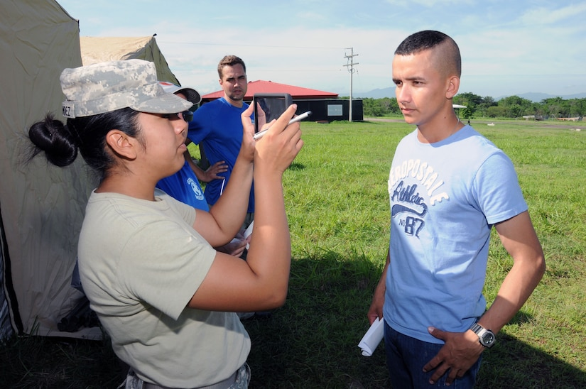 U. S. Army Pfc. Anisa Hernandez, MEDEL human resource specialist, takes a photo of a hurricane victim after she entered his information into the Global MedAid program.  In preparation for the 2014 hurricane season, the Joint Task Force-Bravo Medical Element (MEDEL) conducted a humanitarian assistance/disaster response (HA/DR) exercise at Soto Cano Air Base, Honduras June 12, 2014.  The MEDEL's mission was to establish a forward medical treatment operation capable of providing triage, primary care, surgical capabilities, patient holding and evacuation.  As part of this exercise, a suite of mobile technology applications that run on smartphones and tablets were used to enhance the capabilities of the unit: Global MedAid, Medical Application of Speech Translation (MAST) and GeoSHAPE.  (Photo by U. S. Air National Guard Capt. Steven Stubbs)