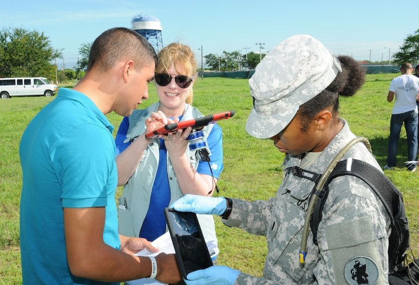 Cynthia Barrigan (left), Telemedicine & Advanced Technology Research Center (TATRC) portfolio manager, communicates with a Spanish-speaking hurricane victim using the Medical Application of Speech Translation (MAST) while U. S. Army 1st Lt. Jewell Hemmings, MEDEL community health nurse, scans the patient's armband with the Global MedAid program.  In preparation for the 2014 hurricane season, the Joint Task Force-Bravo Medical Element (MEDEL) conducted a humanitarian assistance/disaster response (HA/DR) exercise at Soto Cano Air Base, Honduras June 12, 2014.  The MEDEL's mission was to establish a forward medical treatment operation capable of providing triage, primary care, surgical capabilities, patient holding and evacuation.  As part of this exercise, a suite of mobile technology applications that run on smartphones and tablets were used to enhance the capabilities of the unit: Global MedAid, Medical Application of Speech Translation (MAST) and GeoSHAPE.  (Photo by U. S. Air National Guard Capt. Steven Stubbs)