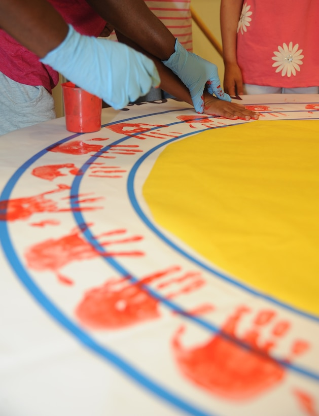 Children at the Keesler Youth Center decorate a banner with their handprints June 13, 2014, at the Youth Center, Keesler Air Force Base, Miss.  The banner will be presented to the Armed Forces Retirement Home on behalf of the Ringling Brothers Circus.  (U.S. Air Force photo by Kemberly Groue)