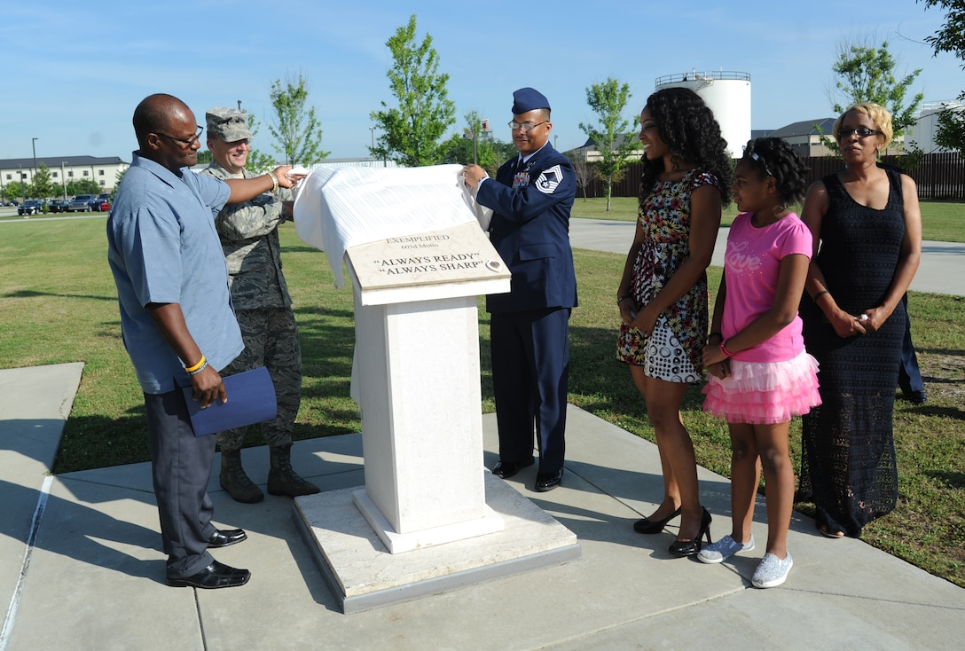 Brig. Gen. Patrick Higby, 81st Training Wing commander, assists family and friends of the late Airman 1st Class Antoine Holt with unveiling a memorial honoring Holt June 12, 2014, in front of Avery Manor at Keesler Air Force Base, Miss.  Holt, a former student in the 334th Training Squadron, lost his life April 10, 2004 while at Balad Air Base, Iraq, when his tent was hit by a mortar attack.  (U.S. Air Force photo by Kemberly Groue)