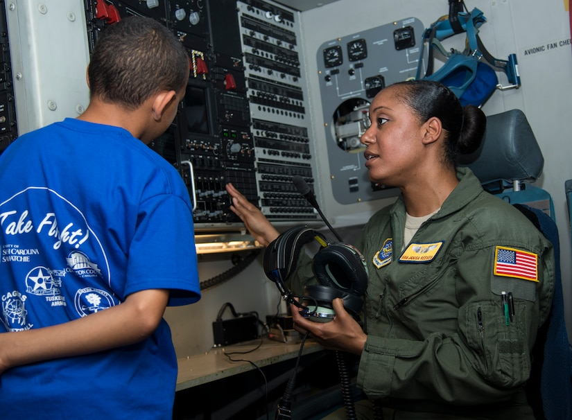 Senior Airman Janisa Reeves, 16th Airlift Squadron loadmaster, explains to a student how voice communication works on a C-17 Globemaster III, June 12, 2014, at Joint Base Charleston, S.C. Students from the Take Flight! Aviation Camp got an inside look at one of JB Charleston's C-17's and also got to hear stories from retired Lt. Col. Robert Hughes, an original Tuskegee Airman. (U.S. Air Force photo/ Airman 1st Class Clayton Cupit)