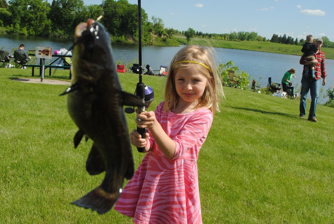 Five-year-old, Sophie Vageline, carries her 3 ounce flathead catfish to a judge for weighing during the 26th Annual Kids' Fishing Derby held June 7, 2014, at Larimore Dam, N.D. More than 160 youngsters registered to compete at the family-friendly event put on by staff members of the Outdoor Recreation Center and the services flight, subordinate units of the 319th Force Support Squadron on Grand Forks Air Force Base, N.D. (U.S. Air Force photo/Staff Sgt. Luis Loza Gutierrez)