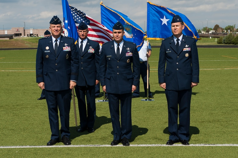 """From left; Lt. Gen. John W. """"Jay"""" Raymond, U.S. Strategic Command's Joint Functional Component Command for Space and 14th Air Force (Air Forces Strategic) commander; Chief Master Sgt. Craig S. Hall, 460th Space Wing command chief, Col. John Wagner, 460th SW commander; and Col. Dan Wright stand together during the presentation of Wagner as the new commander of the 460th Space Wing during the change of command ceremony June 12, 2014, at the all-purpose field on Buckley Air Force Base, Colo. This event signals Wagner's assumption of command from Wright, who assumed command June 2013. (U.S. Air Force photo by Senior Airman Phillip Houk/Released)"""