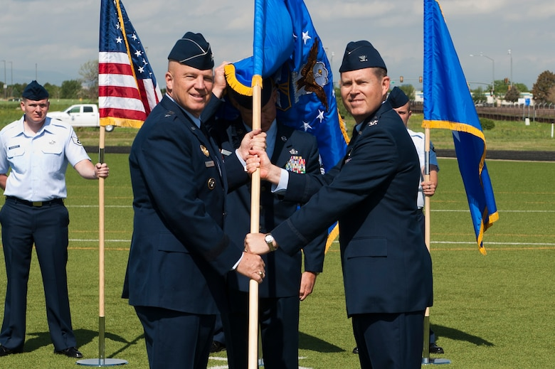 """Col. Dan Wright, right, relinquishes his command of the 460th Space Wing to Lt. Gen. John W. """"Jay"""" Raymond, U.S. Strategic Command's Joint Functional Component Command for Space and 14th Air Force (Air Forces Strategic) commander, left, during the change of command ceremony June 12, 2014, at the all-purpose field on Buckley Air Force Base, Colo. Wright served as the commander of the 460th Space wing since June 2013, where he lead the base through challenging fiscal times, several deaths, and began several actions to localize medical services. (U.S. Air Force photo by Senior Airman Phillip Houk/Released)"""