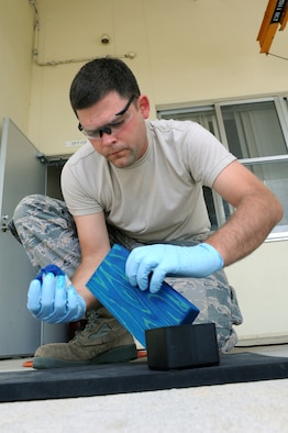 U.S. Air Force Staff Sgt. Jonathan Corbitt, 18th Component Maintenance Squadron avionics team leader, stains a piece of wood in preparation for engraving on Kadena Air Base, Japan, June 12, 2014. Corbitt has been working with wood for about 15 years, and held a job remodeling homes before enlisting into the Air Force. He said working on creative, constructive projects is a relaxing hobby he has always enjoyed. (U.S. Air Force photo by Airman 1st Class Zade C. Vadnais)