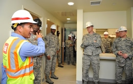 Jamie Hagio, U.S. Army Corps of Engineers Osan Resident Office resident engineer, discusses the construction progress of a new senior NCO dormitory on Osan Air Base, Republic of Korea, June 5, 2014. The facility is one of several projects managed by the USACE to enhance mission readiness and quality of life on base.