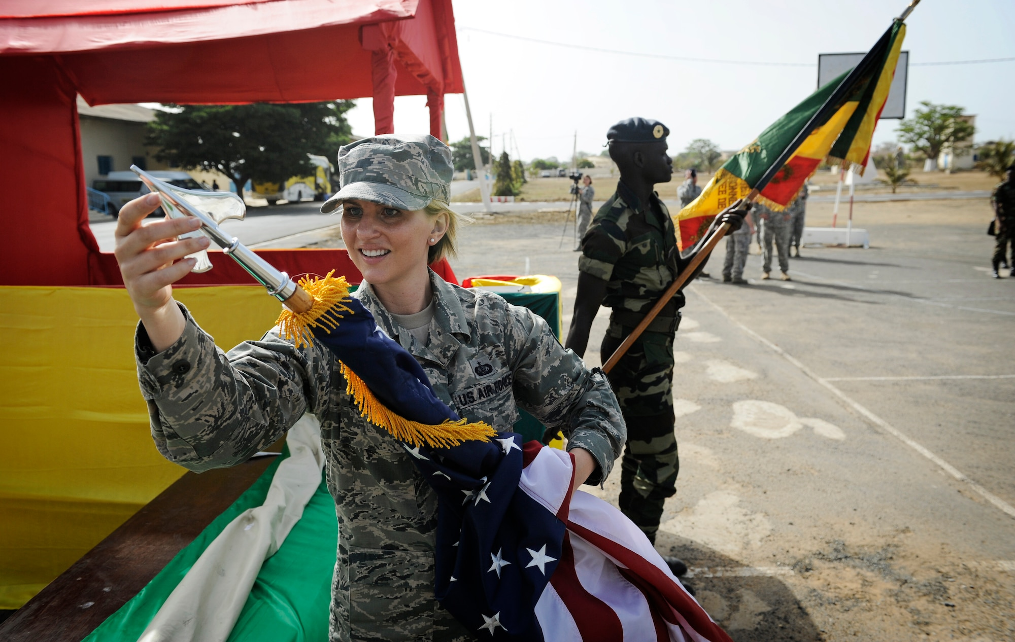 Staff Sgt. Jessica Ancheta, U.S. Air Forces in Europe and Air Forces Africa protocol specialist, prepares the U.S. flag for the opening ceremony of African Partnership Flight in Dakar, Senegal, June 16, 2014. USAFE-AFAFRICA Airmen are in Senegal for APF, a program designed to improve communication and interoperabilty between regional partners in Africa. The African partners include Senegal, Togo, Burkina Faso, Benin, Ghana, Mauritania, Nigeria and Niger with the U.S. helping with organization. (U.S. Air Force photo/ Staff Sgt. Ryan Crane)