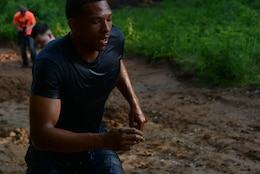 Petty Officer Second Class Joshua Francis, member of one of the Naval Health Clinic Quantico teams, runs out of the second mud obstacle of the Run Amuck course on June 14, 2014. Ten teams competed in the Warrior Challenge.