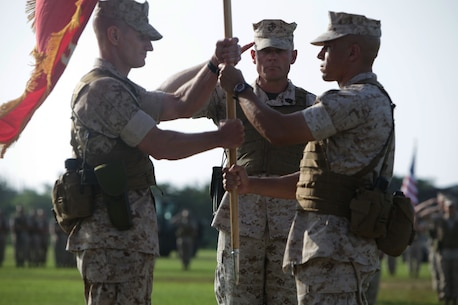 Lieutenant Colonel Eric C. Malinowski, left, receives the Combat Logistics Battalion 31 flag from Lt. Col. Omar J. Randall, a native of the Bronx, New York, during a change of command ceremony at the Camp Hansen's parade deck, June 12. Malinowski, a native of Portsmouth, New Hampshire, assumed command of the battalion after serving at the Pentagon with Headquarters Marine Corps, Installation & Logistics, Logistics Plans and Operations Branch from July 2013 to May 2014. Randall served as the commanding officer since June 2012 and his next assignment will be as a Marine Corps liaison to the United States Agency for International Development in Washington, D. C.  The 31st MEU is the force of choice in the Asia-Pacific region and is the only continuously forward-deployed MEU.