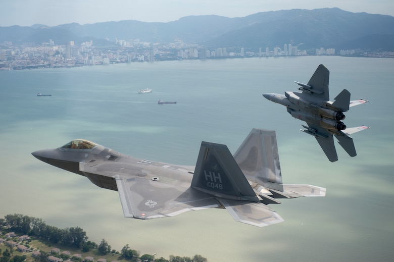 U.S. Air Force F-15 Eagle from the 131st Fighter Squadron, 104th Fighter Wing, Barnes Air National Guard Base, Mass., breaks away from formation with a U.S. Air Force F-22 Raptor from the 154th Wing, Joint Base Pearl Harbor-Hickam, Hawaii, as the two aircraft line up for landing at Royal Malaysian air force P.U. Butterworth, Malaysia, during Cope Taufan 14, June 16, 2014. Cope Taufan is a biennial large force employment exercise taking place June 9 to 20 designed to improve U.S. and Malaysian combined readiness. (U.S. Air Force photo by Tech. Sgt. Jason Robertson/Released)