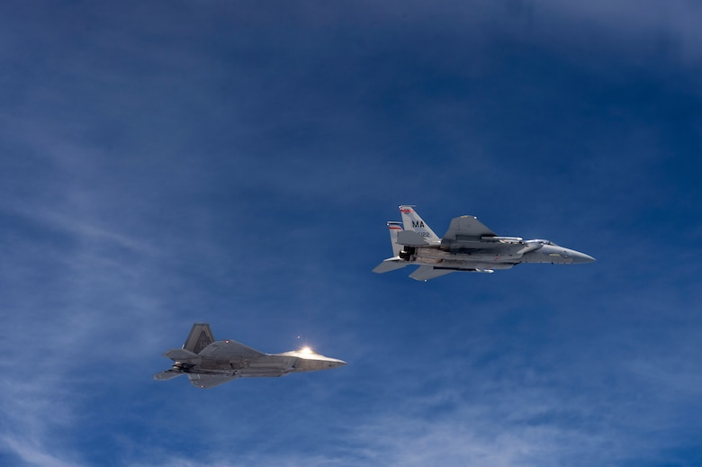 A U.S. Air Force F-22 Raptor from the 154th Wing, Joint Base Pearl Harbor-Hickam, Hawaii, and U.S. Air Force F-15 Eagle from the 131st Fighter Squadron, 104th Fighter Wing, Barnes Air National Guard Base, Mass., fly over Penang, Malaysia, during Cope Taufan 14, June 16, 2014. Cope Taufan is a biennial large force employment exercise taking place June 9 to 20 designed to improve U.S. and Malaysian combined readiness. (U.S. Air Force photo by Tech. Sgt. Jason Robertson/Released)