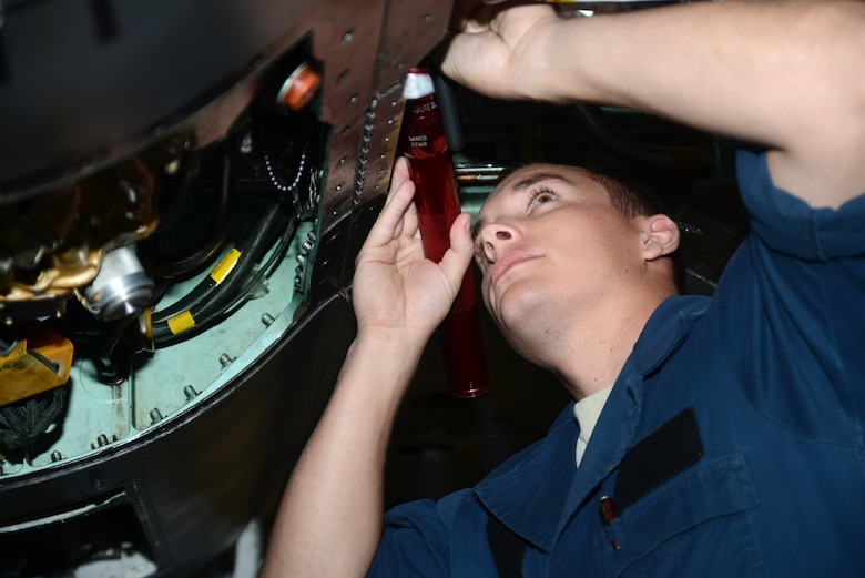 Senior Airman Wes Atkins, 366th Equipment Maintenance Squadron crew chief, fixes the underside of a F-15E Strike Eagle June 6, 2014, at Mountain Home Air Force Base, Idaho. Atkins assisted Idaho state police with a major accident and attruibutes his quick thinking to the risk-management training members receive during the 101 Critical Days of Summer. He urges everyone to be safe when driving on the interstate. (U.S. Air Force photo by Senior Airman Benjamin Sutton/Released)