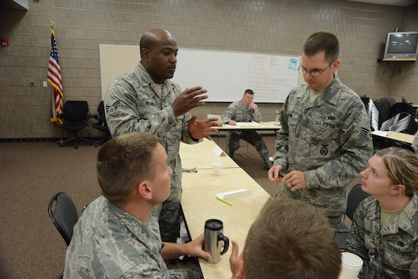 Senior Airman Roy Roach III, of the North Dakota Air National Guard's 119th Medical Group, standing left, offers an opinion for group discussion during an Airman Leadership School (ALS) class at Guard's Air Base, Fargo, N.D., June 12, 2014, as instructor Tech. Sgt. James Richey monitors the activity on the background. The five-week ALS course is among the first in the country being offered by active duty instructors at an Air National Guard base. Instructors traveling to students' location are a cost effective way of conducting training. (U.S. Air National Guard photo by SMSgt. David H. Lipp/Released)