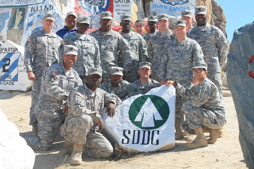 """Members of the 841st Transportation Battalion Deployment and Distribution Support Team, stand behind the SDDC rock that will establish the """"Transporters"""" as one of the pillars supporting the commands at Fort Irwin, Calif. (U.S. Army photo/ Cpl. Denis Ortizrosa)"""
