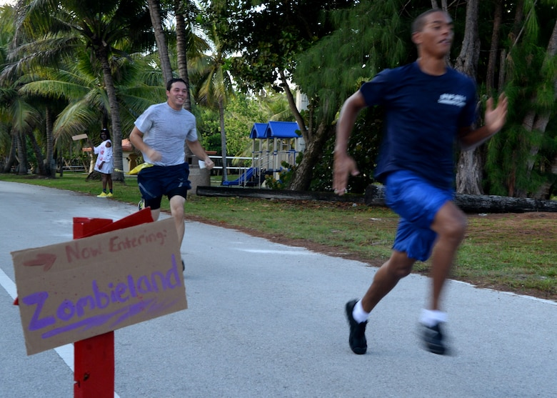 """Runners sprint to the finish line during a Zombie 5K Fun Run June 11, 2014, at Tarague Beach on Andersen Air Force Base, Guam. The first male and female that finished the run without losing a """"life"""" represented by yellow flags that hung from their belts received a trophy and the """"zombie"""" who captured the most """"lives"""" won a trophy. (U.S. Air Force photo by Airman 1st Class Amanda Morris/Released)"""