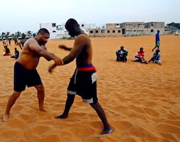 Kelly Grissom, a Brazilian Jujitsu instructor, demonstrates a technique on a Senegalese man in Senegal, Nov. 2013. Kelly Grissom co-founded the Lion Heart Initiative, a plan to teach mixed martial arts to young urban youth of Senegal, West Africa, and create better opportunities for them.