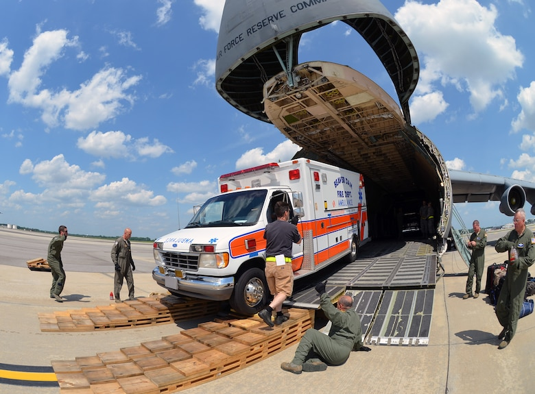Airmen from the 337th Airlift Squadron load an ambulance and two fire trucks onto a C-5 Galaxy, June 9, 2014, on Joint Base Charleston, S.C., June 9, 2014. This Denton Amendment mission delivered the vehicles to Managua, Nicaragua on behalf of the Wisconsin/Nicaragua Partners of the Americas Inc. (U.S. Air Force photo/Staff Sgt. Kelly Goonan)