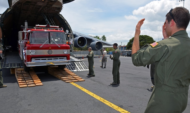 Senior Airman Michael Buchanan, 337th Airlift Squadron loadmaster, marshals a fire truck off a C-5 Galaxy, June 10, 2014, in Managua, Nicaragua. This Denton Amendment mission delivered an ambulance and two fire trucks to Nicaragua on behalf of the Wisconsin/Nicaragua Partners of the Americas Inc. (U.S. Air Force photo/Staff Sgt. Kelly Goonan)