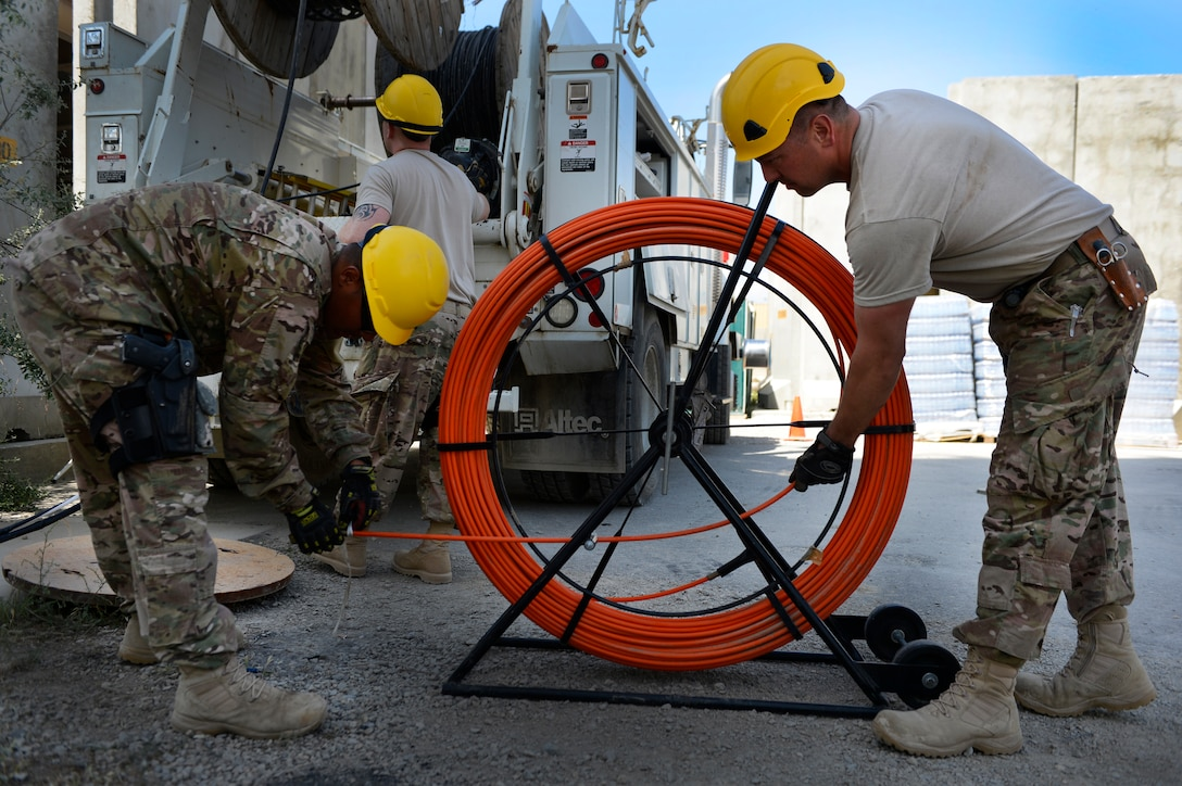 Staff Sgt. Lawence Santos (left) and Senior Airman Ariel Roldan, prepare the duct rod before running a cable May 15, 2014, at Bagram Airfield, Afghanistan. The cable is being used at the Air Traffic Control Tower and Command Post to provide connections for several necessary communication supports needed throughout the base. Santos and Roldan are Combined Air and Space Operations Center Engineering and Installations cable and antenna technicians deployed from the 212th Engineering and Installation Squadron, Otis Air National Guard Base, Mass. (U.S. Air Force photo/Senior Airman Sandra Welch)
