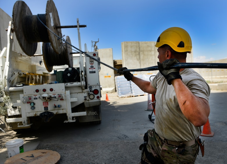 Staff Sgt. Lawence Santos pulls cables May 15, 2014, at Bagram Airfield, Afghanistan. The cable is being used at the air traffic control tower and command post to provide connections for several necessary communication supports needed throughout the base. Santos is a Combined Air and Space Operations Center Engineering and Installations cable and antenna technician. (U.S. Air Force photo/Senior Airman Sandra Welch)