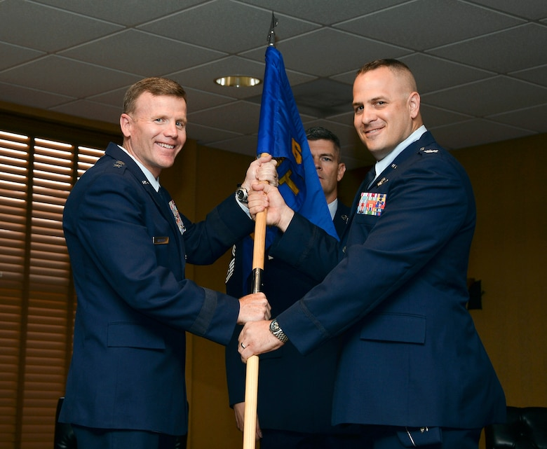 Lt. Gen. Tod Wolters, Commander 12th Air Force (Air Forces Southern) passes the squadron guideon to Col. James Sheedy during the 612th Theater Operations Group Change of Command Ceremony on Davis-Monthan AFB, Ariz., June 17, 2014.  Sheedy assumed command of the 612 TOG from Col. Jonathan VanNoord. (U.S. Air Force photo by Tech. Sgt. Heather R. Redman/Released)