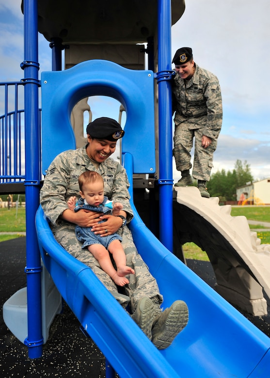 Senior Airmen Abigail, left, and Tori Andrade, 354th Security Forces Squadron members, play at a park with their son, Maximus, June 9, 2014, Eielson Air Force Base, Alaska. The Andrades married in Feb. 2013; they were the first married lesbian couple on base. (U.S. Air Force photo by Senior Airman Ashley Nicole Taylor/Released)