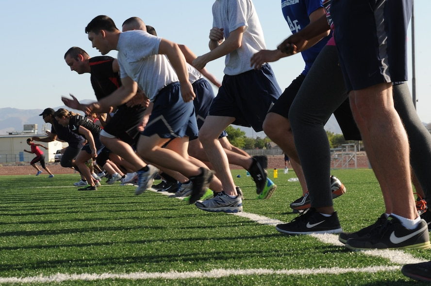 Members of the Nellis community sprint across the Warrior Fitness Center football field during a Warrior Trained Fitness workout June 12, 2014, at Nellis Air Force Base, Nev.  The WTF exercise session was the last to be hosted by Missy Cornish, wife of Col. Barry Cornish, 99th Air Base Wing commander. (U.S. Air Force photo by Tech. Sgt. Taylor Worley)