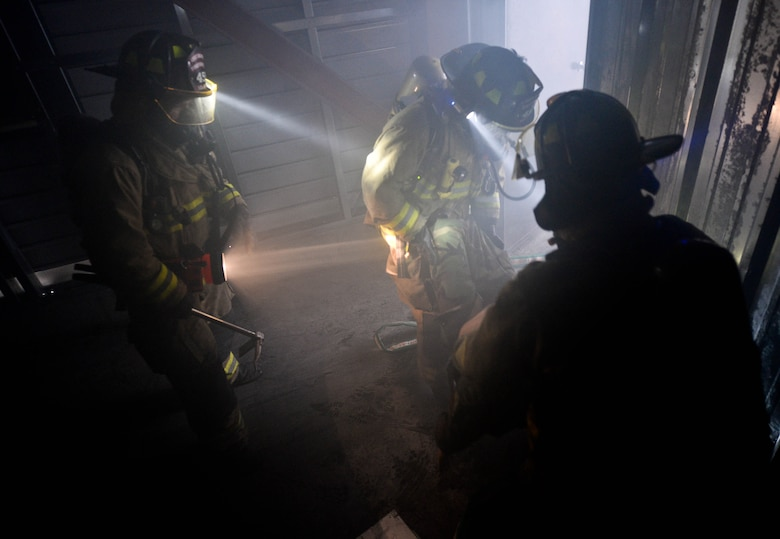 Firefighters assigned to the South Dakota Army National Guard 451st Engineering Detachment Firefighting Team, look for casualties during simulated search and rescue training as part of the 2014 Golden Coyote exercise at Ellsworth Air Force Base, S.D., June 11, 2014. The joint training exercise consists of three-phases and is conducted annually each June. (U.S. Air Force photo by Senior Airman Zachary Hada/Released)