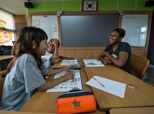 Senior Airman Kayla Dale shares a laugh with two Korean students June 5, 2014, in Pyeongtaek, South Korea. Dale volunteers with other Airmen on Osan Air Base to help Korean students become familiar with English-language skills. Dale is a 51st Maintenance Squadron non-destructive inspector. (U.S. Air Force photo/Staff Sgt. Jake Barreiro)