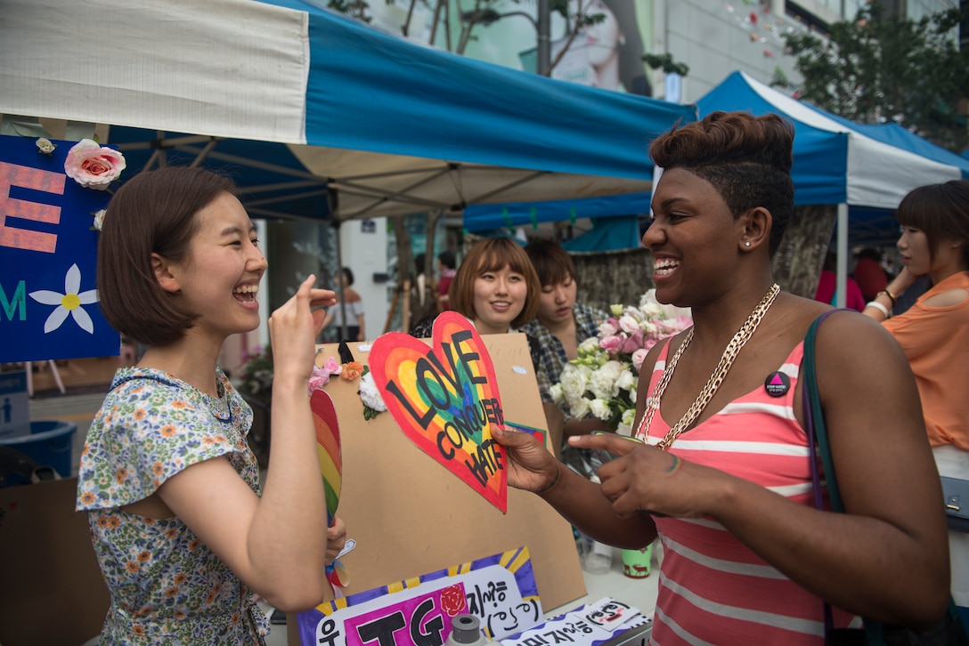 Senior Airman Kayla Dale talks at an information booth at the Gay Pride Parade June 7, 2014, in Seoul, South Korea. Dale, a 51st Maintenance Squadron non-destructive inspector, has been in the Air Force since 2011, first working at Langley Air Force Base, Va., before moving to Osan Air Base in April of 2014. (U.S. Air Force photo/Staff Sgt. Jake Barreiro)