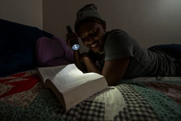 Senior Airman Kayla Dale reads a book in her dorm room June 13, 2014, at Osan Air Base, South Korea. Dale credits her hobbies of reading and writing with keeping her out of trouble and inspiring her to dream big as a child. A lesbian, Dale joined the Air Force after the Don't Ask Don't Tell Repeal Act of 2010, and intends to one day marry and adopt children. Dale is a 51st Maintenance Squadron non-destructive inspector. (U.S. Air Force photo/Staff Sgt. Jake Barreiro)