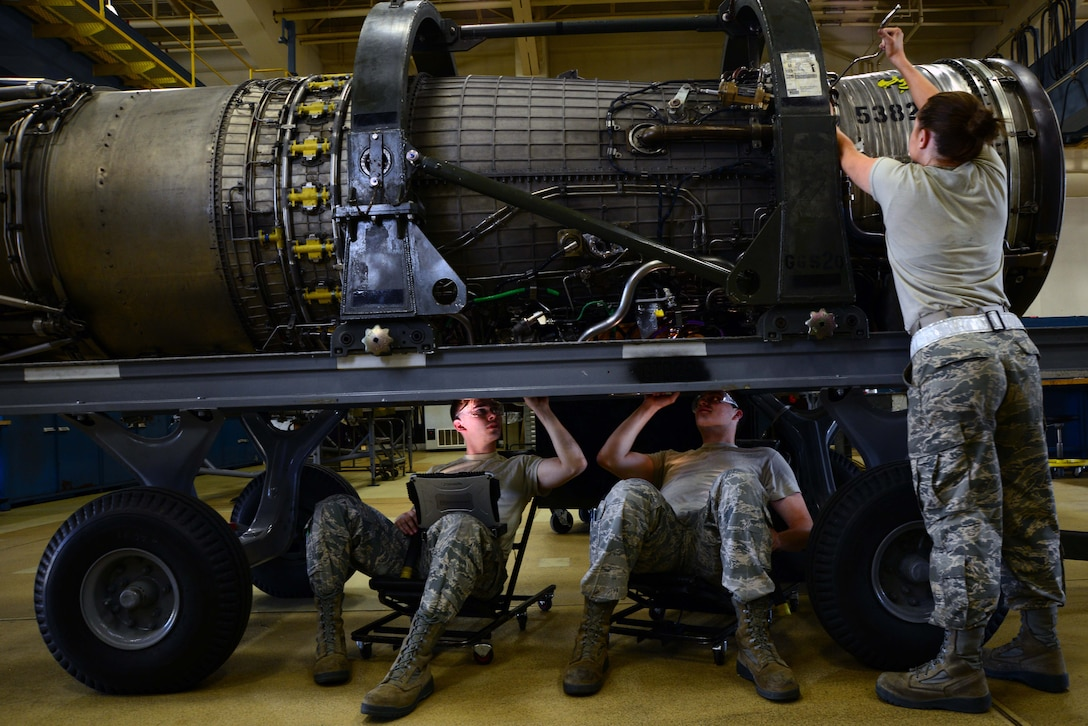 """From left: Airmen 1st Class Tyler Susskind, Robert Reindl and Airman Madison Mitchell, 35th Maintenance Squadron aerospace propulsion journeymen, put the finishing touches on an F-16 Fighting Falcon engine June 6, 2014, at Misawa Air Base, Japan. Aerospace Propulsion is known as """"props,"""" and is responsible for all engine maintenance for not only Misawa AB, but Osan and Kunsan Air Bases, South Korea. (U.S. Air Force photo/Senior Airman Derek VanHorn)"""