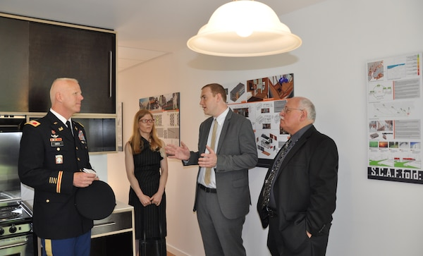 Michael Hogg, project manager, U.S. Army  Corps of Engineers, NY District (second from right), explains interior design features of emergency prototype housing to Col. Paul Owen (left), Commander of the NY District, on June 10, 2014. The units are designed to resettle large numbers of people quickly in an urban area in the event of a major coastal storm or disaster. At extreme right is Nicholas Peluso, director, constructability and bid packaging, NYC Dept. of Design and Construction; in background is Cynthia Barton, project manager, NYC Office of Emergency Management. The Army Corps of Engineers is serving as project manager.