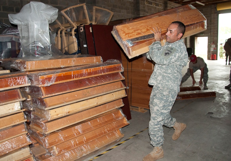 U.S. Army Sgt. 1st Class Chris Gomez, New Horizons Civil Affairs offloads donated supplies June 2, 2014, at the BDF Price Barracks in Ladyville, Belize. The civil affairs team worked with various non-government organizations, or NGOs, that donated school and medical supplies and furniture, and they also assisted during medical readiness training exercises in the northern Corozal District and southern Toledo District. (U.S. Air Force photo by Tech. Sgt. Kali L. Gradishar/Released)