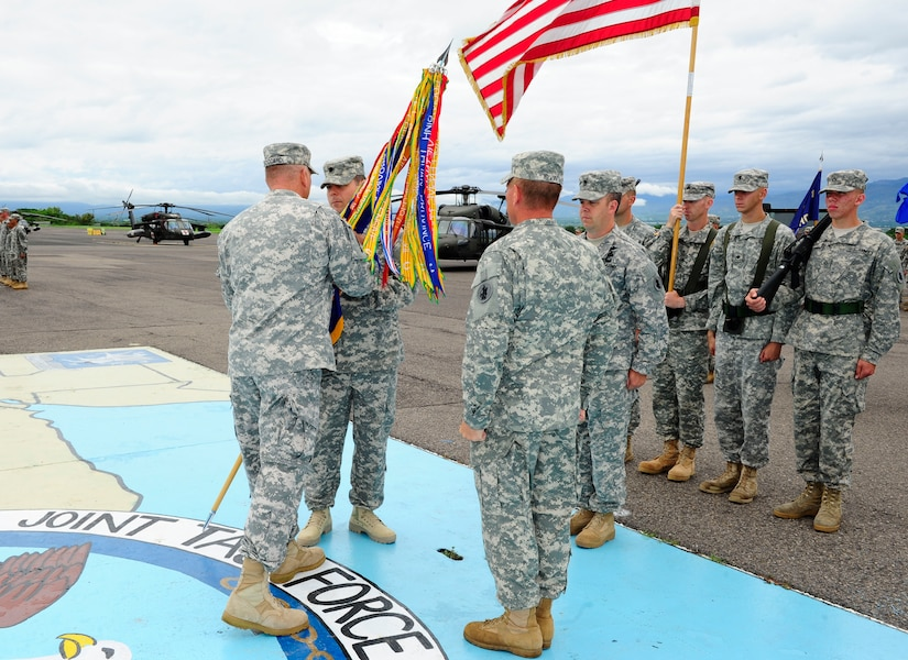 U. S. Army Lt. Col. Shane Mendenhall assumes command of the 1-228th Aviation Regiment at Soto Cano Air Base, Honduras by accepting the guidon from U. S. Army Col. Thomas Boccardi, the Joint Task Force-Bravo commander, June 16, 2014. Mendenhall assumed command from outgoing commander U. S. Army Lt. Col. E. J. Irvin, II. The 1-228th Aviation Regiment, under U. S. Army South, has directly supported the U. S. Southern Command's engagement and security cooperation strategy.  This one-of-a-kind battalion provides heavy lift, medical evacuation, general aviation and VIP support spanning the area of responsibility in support of Joint Task Force-Bravo.  The regiment has actively participated in counter narcotics missions and humanitarian assistance/disaster relief support throughout Central America.  (Photo by Martin Chahin)